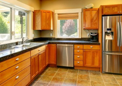 Spacious kitchen room with tile floor, wood cabinets and steel appliances